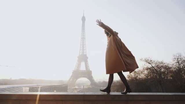 Side view beautiful happy woman doing fun dance walk at romantic sunset Eiffel Tower sky panorama in Paris slow motion.