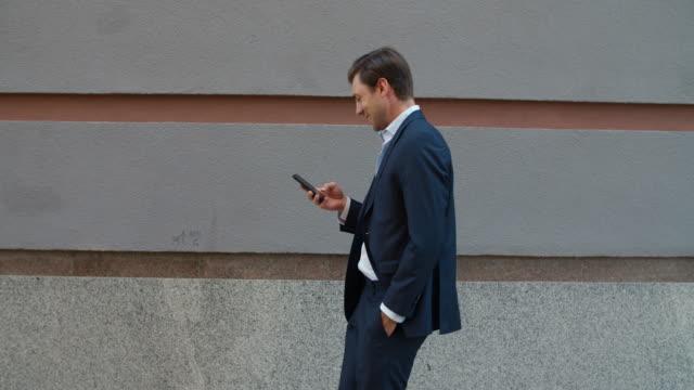 side view affärsman walking med telefon. man tittar in smartphone utomhus - kostym sida bildbanksvideor och videomaterial från bakom kulisserna