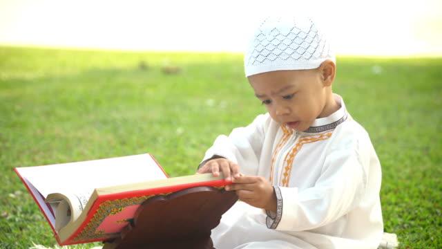 stockvideo's en b-roll-footage met zijaanzicht: vrolijke jongen in traditionele kleding probeert te lezen van de koran in openbaar park door hemzelf - koran