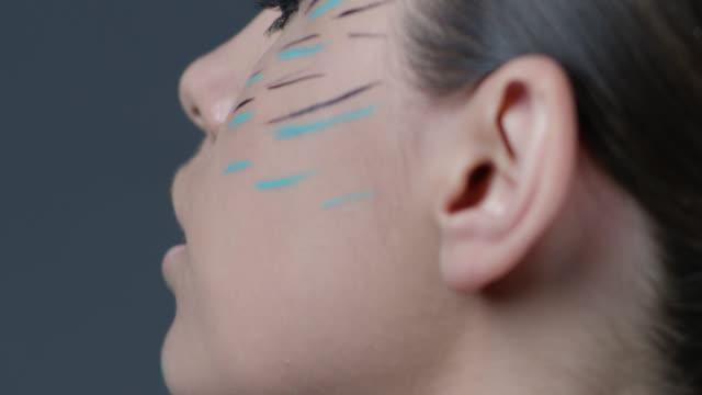 サイド ビューはカメラに目を向けてモデルのクローズ アップ。ファッションのビデオ。 - グリースペイント点の映像素材/bロール