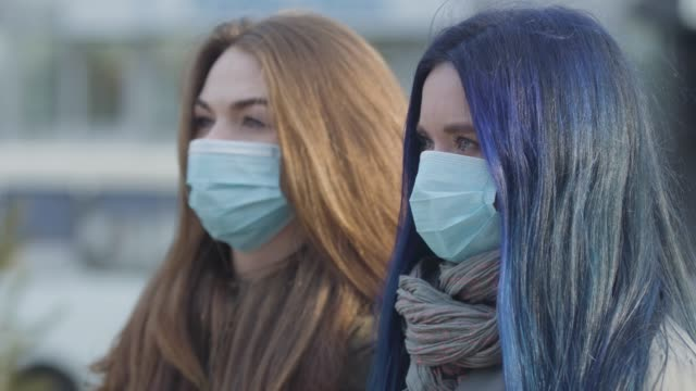 Side view close-up of two anxious women in protective masks looking away. Women standing on city street. Focus changes from blue-haired girl to brunette woman. Global danger, hazard, virus. Side view close-up of two anxious women in protective masks looking away. Women standing on city street. Focus changes from blue-haired girl to brunette woman. Global danger, hazard, virus. blue hair stock videos & royalty-free footage