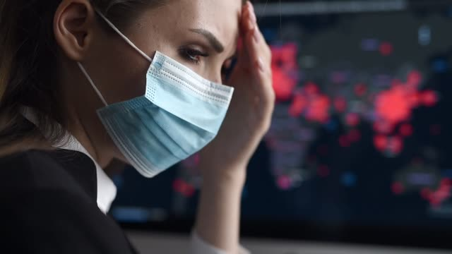 Side view close-up portrait of a young woman in disposable medical facial mask holding her head and looking at the epidemic map of the coronavirus Covid 19 pandemic on a computer