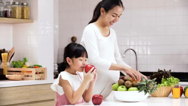 side view: daughter help pregnant mother in modern kitchen - один родитель стоковые видео и кадры b-roll