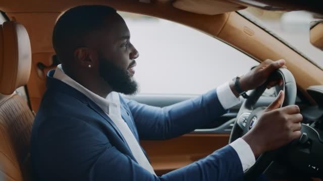 vídeos de stock, filmes e b-roll de motorista de visão lateral dançando ao volante. homem movendo as mãos de frente para o carro - veículo terrestre