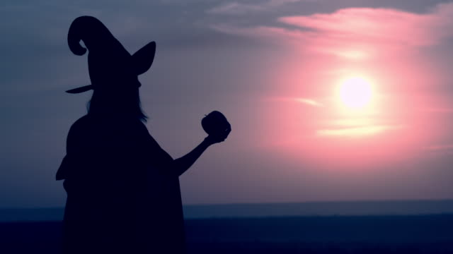 side view evil sorceress in hat offers a magic apple – film