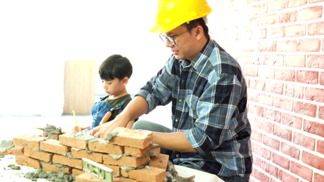 Side view: father teaching how to lay  brick on a new house to her son as workshop