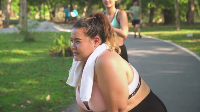 side view: female large build athlete so tried but her friend is coming to give the passion in a public park - trentenne video stock e b–roll