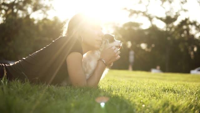 vidéos et rushes de images de vue latérale d'une jeune femme blanche en noir t shirt couché sur l'herbe avec son petit chien et examiner tout droit ensemble pensivement. parc verdoyant, l'été, soleil brille - femme seule s'enlacer
