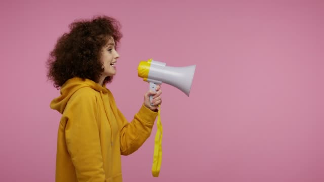 Side view, girl afro hairstyle in hoodie talking with megaphone, proclaiming news, announcing advertisement