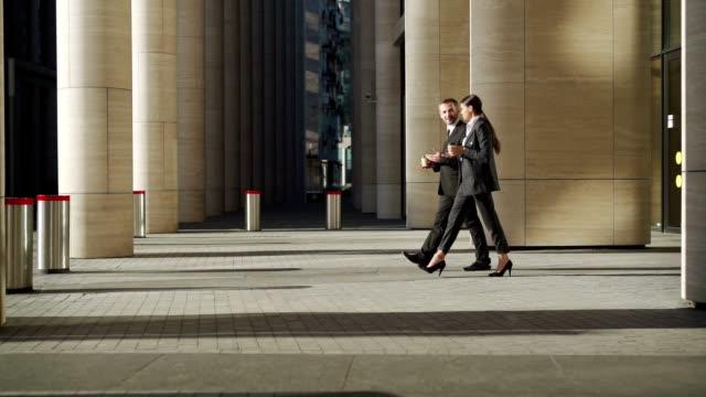 sidovy låsning skott av två leende affärsfolk, medelålders man och ung kvinna i höga klackar lämnar kontorsbyggnad, promenader med kaffe i slow motion och pratar vänligt efter jobbet - kostym sida bildbanksvideor och videomaterial från bakom kulisserna