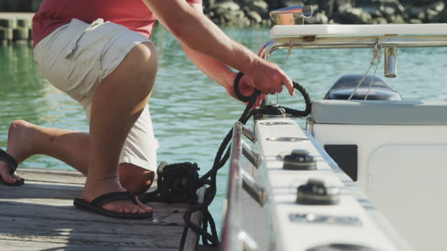 Side view low section of a Caucasian man untying a rope on the boat harbor side Side view low section of a Caucasian man, enjoying his time on a promenade, kneeling on a jetty, untying a rope on the boat, on a sunny day, in slow motion mid adult men stock videos & royalty-free footage