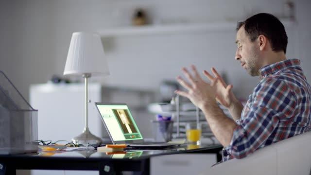 自宅でラップトップコンピュータ上でビジネスビデオ通話を持っている自信のある中年男性のサイドビューミディアムショット。机に座っている同僚と話しながらジェスチャーするビジネス� - オンライン会議点の映像素材/bロール