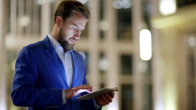 Side view medium shot of middle aged businessman in suit using application on tablet computer outdoors in evening