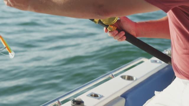 Side view mid section of a Caucasian man fishing on a boat Side view mid section of a Caucasian man, enjoying his time on a boat, holding and using a fishing rod, on a sunny day, in slow motion mid adult men stock videos & royalty-free footage