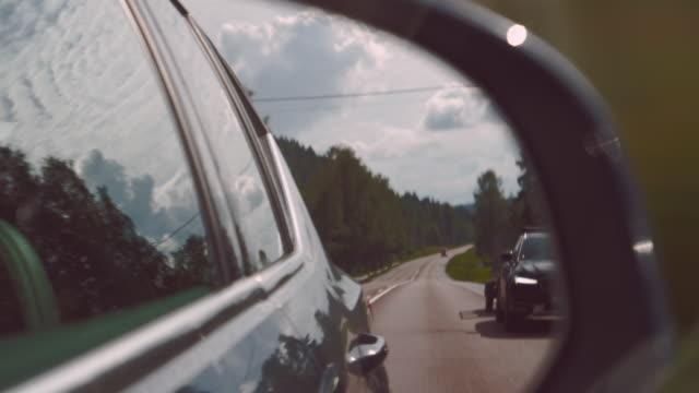 vidéos et rushes de marques de route de miroir de vue latérale et route de goudron avec la voiture de dépassement - vue latérale