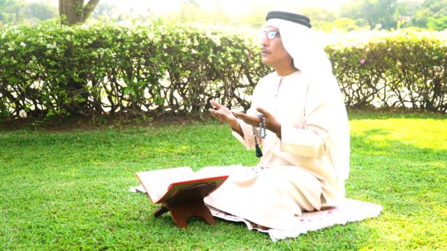 stockvideo's en b-roll-footage met zijaanzicht: moslim grootvader lezen quran in openbaar park in ochtend - koran