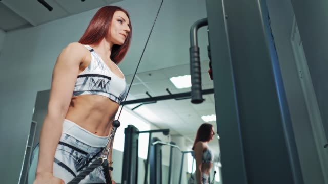 Bидео Side view of a beautiful sportswoman in fitness center.