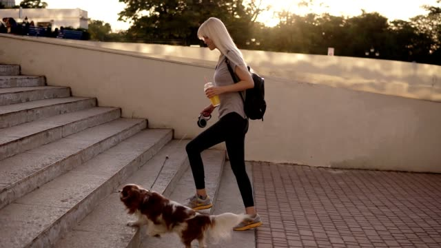 Side view of a blonde woman walking with a dog at the leash in the city. Going upstairs in the park, holding an orange drink in plastic cup Side view of a blonde woman walking with a dog at the leash in the city. Going upstairs in the park, holding an orange drink in plastic cup. leash stock videos & royalty-free footage