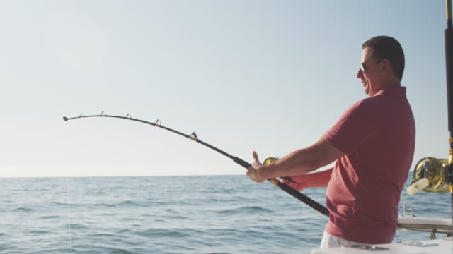 Side view of a Caucasian man fishing on boat Side view of a Caucasian man, enjoying his time on a boat, holding and using a fishing rod, on a sunny day, in slow motion mid adult men stock videos & royalty-free footage