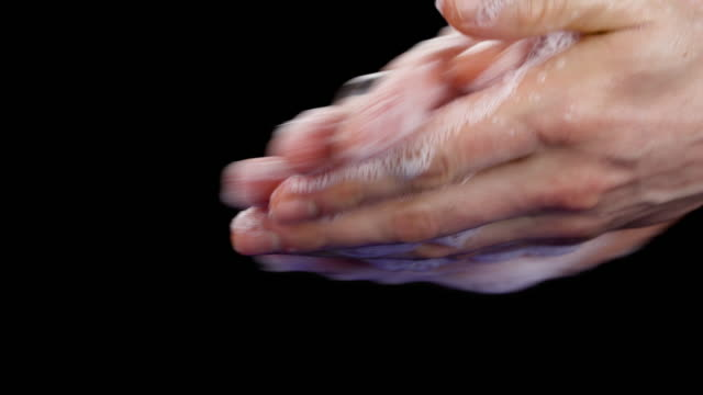 Side view of a caucasian man hands. Lather hands by rubbing them together with the soap bar. Closeup. Isolated on the black background.