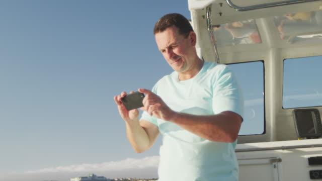 자신의 휴대 전화와 함께 사진을 찍는 보트에 백인 남자의 측면 보기 - 중년 남자 스톡 비디오 및 b-롤 화면