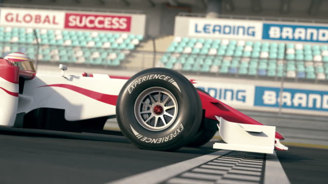 Side view of a formula one race car driving over finish line in slow motion