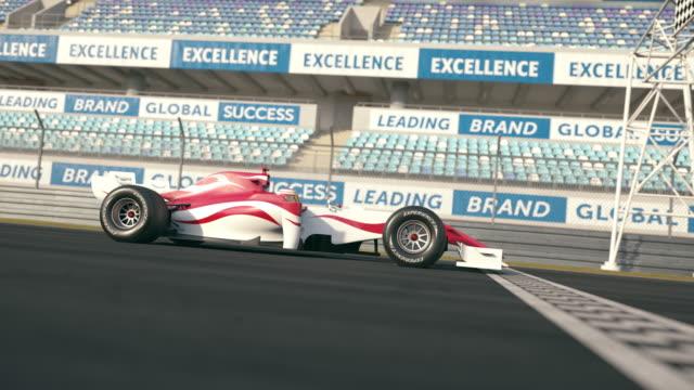 슬로우 모션에서 결승 선을 통해 운전 하는 포뮬러 원 레이스 자동차의 측면도 - formula 1 스톡 비디오 및 b-롤 화면