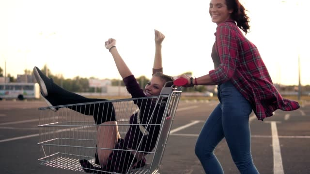 Side view of a happy young woman pushing a grocery cart with her girlfriend inside in the parking by the shopping mall during sunset. Slowmotion shot Side view of a happy young woman pushing a grocery cart with her girlfriend inside in the parking by the shopping mall during sunset. Slowmotion shot. woman pushing cart stock videos & royalty-free footage