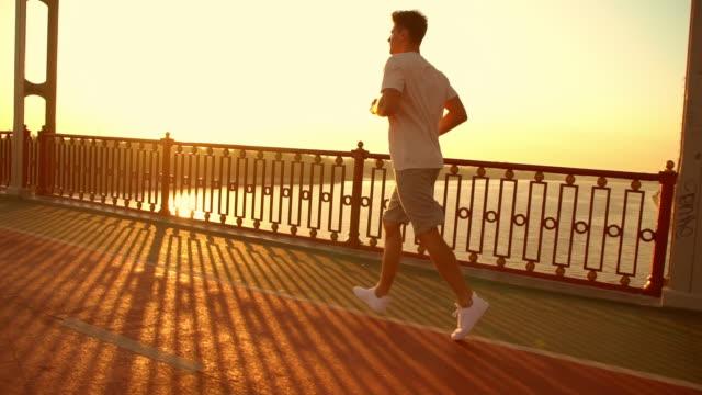 stockvideo's en b-roll-footage met zijaanzicht van een mannelijke joggen - wit t shirt