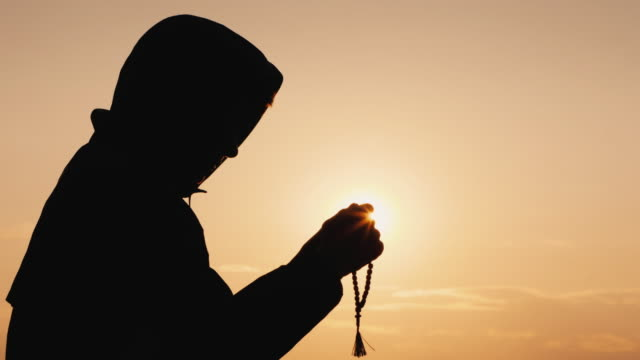 Side view of a man in the hood, sifting through the rosary at sunset video