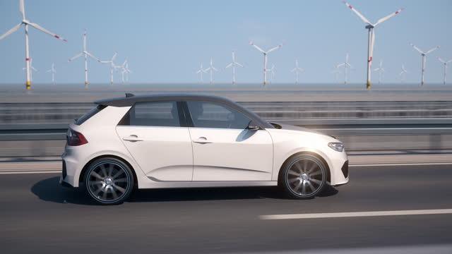 風力タービンを背景に運転する自動運転自動電気自動車の側面図 - 車点の映像素材/bロール