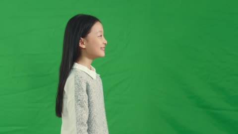 side view of a smiling asian girl side view of a smiling little asian girl against green background medium shot stock videos & royalty-free footage