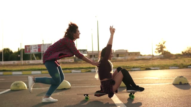 Side view of a woman with her hands raised up sitting on a longboard while her friend is pushing her behind and running during sunset. Enjoying life. Lens flare. Slowmotion shot video