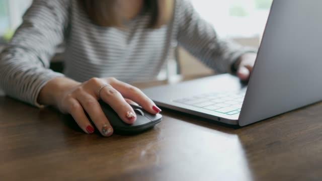 seitenansicht der hand einer frau, die mit wireless-maus auf dem holztisch im café - computermaus stock-videos und b-roll-filmmaterial