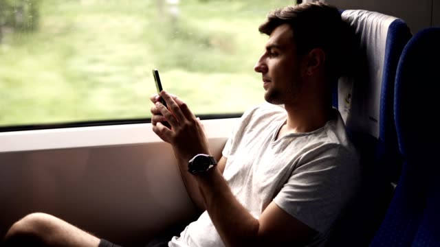 side view of a young, handsome man travels by modern train. sitting next to the window and looking at his mobile phone. slight natural train shaking. casual clothes. nature landscape in window - uomo nostalgia video stock e b–roll