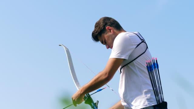 vidéos et rushes de vue de côté d'un jeune homme se préparant à tirer de l'arc - tir à l'arc
