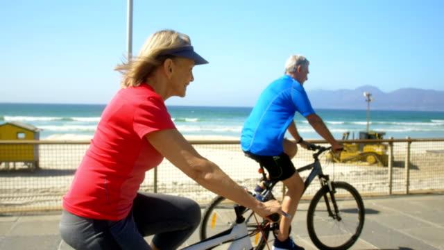 Seitenansicht des aktiven servierten kaukasischen Ehepaares, das Fahrrad auf einer Promenade am Strand 4k reitet – Video