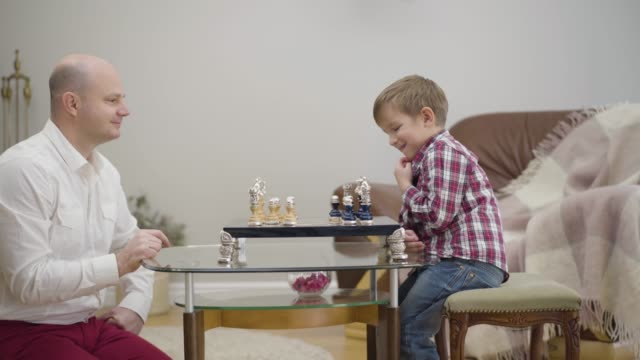 Side view of adult Caucasian man teaching little son to play chess. Little cute boy learning with father at home. Unity, intelligence, education.