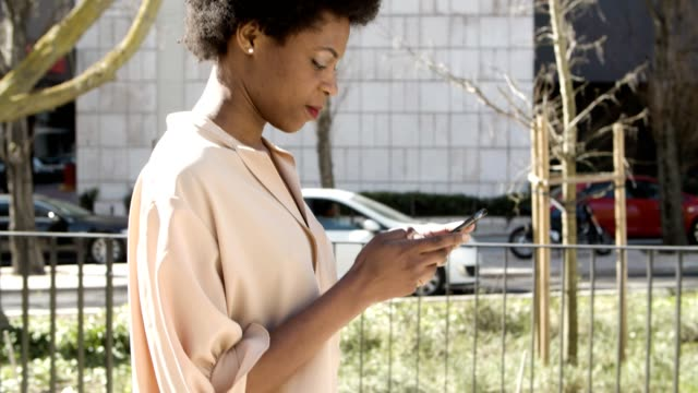 Side view of African American woman texting on smartphone