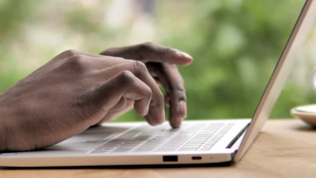 side view of african hands typing on laptop - terrazza video stock e b–roll