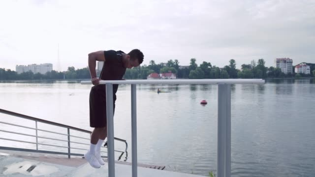 Side view of african man doing triceps dip exercise