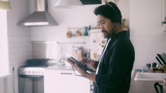 アジア人男性のサイドビューは、電話会議中にデジタルタブレットを使用しています - テレビ会議 日本人点の映像素材/bロール
