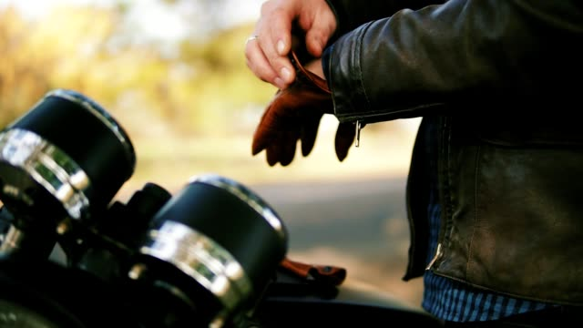 side view of an unrecognizable motorcyclist taking brown leather gloves and wearing special leather mitts for riding in slow motion - rękawiczka filmów i materiałów b-roll