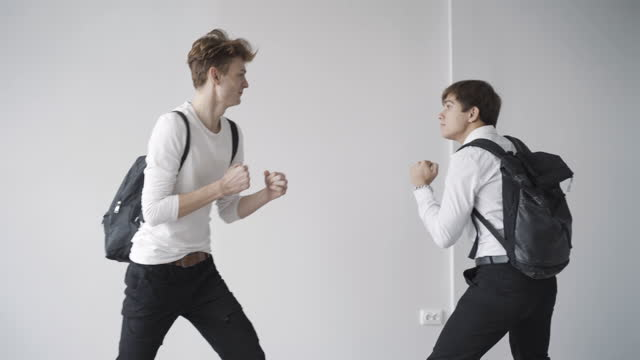 Side view of angry teenagers arguing and fighting in school corridor. Two Caucasian students pushing and hitting. Adolescent learners fight indoors. Anger and adolescence concept.