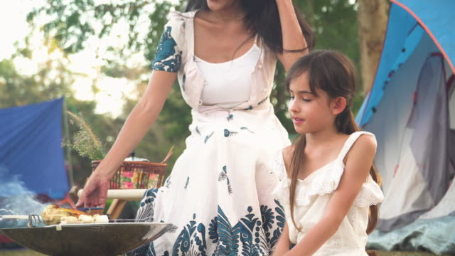 Side view of Asian mother and mixed-race daughter wearing causal clothes travel camping together in a forest, Happy and relax woman reading a book while teenage girl cooking BBQ is in front of a tent. Concept of adventure family at the weekend.