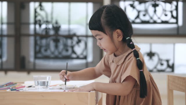 Side view of Asian preschool girl painting with brush