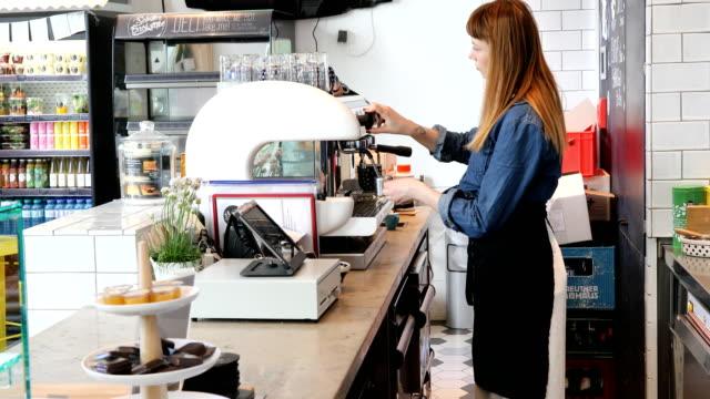 カフェテリアでコーヒーを準備するバリスタの側面図 - バリスタ点の映像素材/bロール