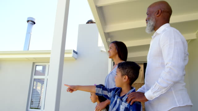 Side view of black family standing on porch and looking away in a comfortable home 4k