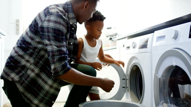 Side view of black father and son washing clothes in washing machine at comfortable home 4k Side view of black father and son washing clothes in washing machine at comfortable home. Black father and son putting clothes in washing machine 4k chores stock videos & royalty-free footage