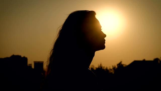 stockvideo's en b-roll-footage met zijaanzicht van zwarte silhouet van de vrouw poseren in verspreide zonsondergang licht op plattelandsachtergrond - vrouwelijkheid